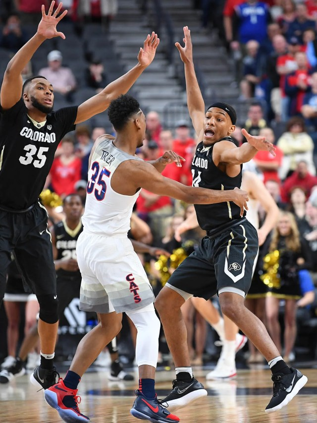 Arizona Wildcats guard Allonzo Trier (35) passes the ball out of the double coverage of Colorado Buffaloes forward Dallas Walton (35) and forward Tory Miller-Stewart (14) during a quarterfinal match of the Pac-12 Tournament at T-Mobile Arena.