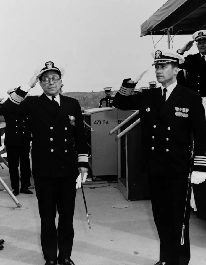 Rear Admiral William F. Petrovic, USN, left, Commander, Puget Sound Naval Shipyard; and Captain Robert E. McClinton, USN, salute at the commissioning of the fifth USS Detroit in 1970.