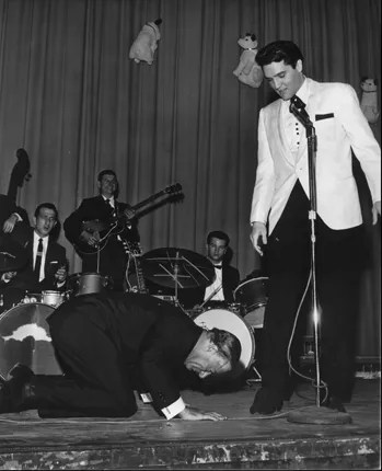Comedian George Jessel hit the stage in an exaggerated salaam to the King of rock and roll at Elvis's evening performance at Ellis Auditorium February 25, 1961. Jessel, the master of ceremonies, could not make it to the earlier matinee performance because of an airline strike. Elvis Presley Day began earlier with a luncheon honoring the singer at Hotel Claridge. More than $50,000 was raised for charity from the events.