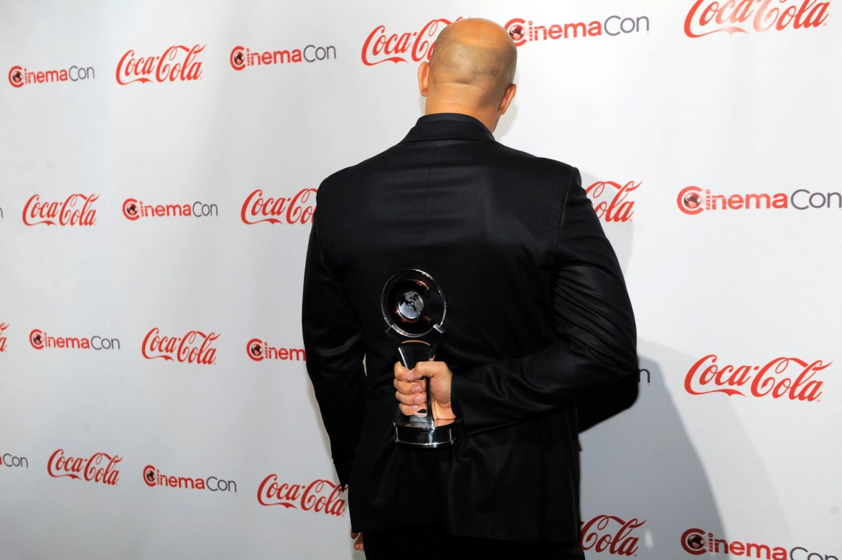Guess who? Vin Diesel, recipient of the Action Star of the Year Award, hides from photographers as he holds his award at the CinemaCon Big Screen Achievement Awards in 2011.