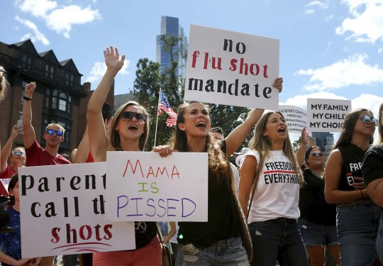 Maria Harvey and her sister Ashley Makridakis  protest mandatory flu vaccinations outside the Massachusetts Statehouse on Aug. 30 in Boston. Public health authorities say flu shots are very important this year to avoid overburdening the health system amid the coronavirus pandemic.