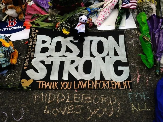 A large sign with the names of the Boston Marathon bombing victims and thanking law enforcement is placed by a Boston Bruins hockey fan at a makeshift memorial for victims near the site of the bombings in Boston, Mass., on April 21.