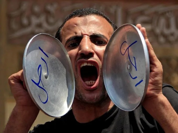 """An opponent of Morsi chants slogans as he holds pot covers with Arabic that reads, """"Leave."""""""