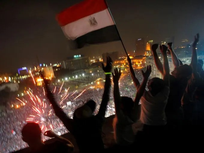 Egyptians wave a national flag as fireworks light the sky over Tahrir Square, where hundreds of thousands opponents of  President Mohammed Morsi celebrate in Cairo.