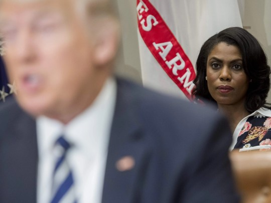 Omarosa Manigault Newman, then White House Director of Communications for the Office of Public Liaison, sits behind President Trump.