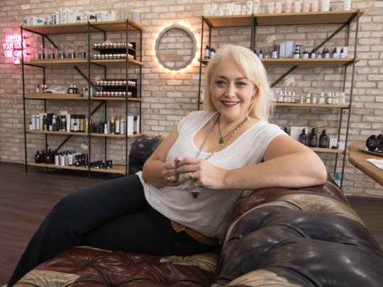 London Beauty owner Kathleen London relaxes in her newly opened downtown Brighton cosmetics shop Tuesday, Aug. 21, 2018.