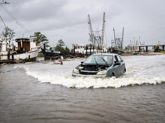 A motorist drives through a flooded area in the Swan Quarter harbor in Swan Quarter, North Carolina.