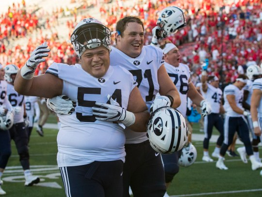 Brigham Young's defensive liner Merrill Taliauli (54) and offensive lineman Austin Hoyt celebrate after their side beat Wisconsin.