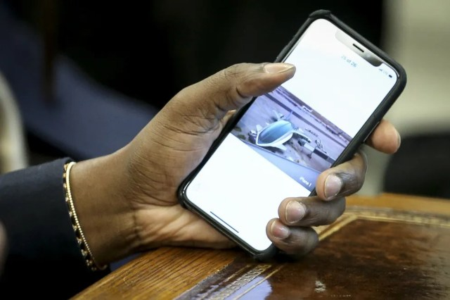 Rapper Kanye West holds his phone with a picture of a plane after he showed it to  President Trump during the meeting.