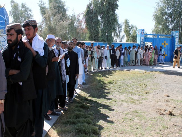 Afghan men line up to cast their votes, outside a polling station during the Parliamentary election in Helmand province, south of Afghanistan, Saturday, Oct. 20, 2018.  Tens of thousands of Afghan forces fanned out across the country to provide security, as voting began Saturday in the elections that followed a campaign marred by relentless violence.