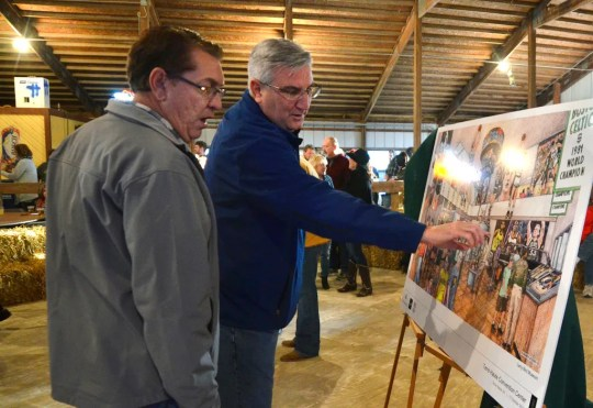 Terre Haute, Ind., Mayor Duke Bennett, left, and Gov. Eric Holcomb (right) note the key attractions of the artist's rendering for the upcoming museum for former basketball player Larry Bird that will be located in the Terre Haute Convention Center after Saturday's press conference to announce the museum at Greg Gibson's home in Terre Haute.