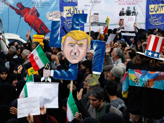 The Iranians hold a poster with a caricature of President Donald Trump during an anti-US. Demonstration of the 39th anniversary of the takeover of the US Embassy.