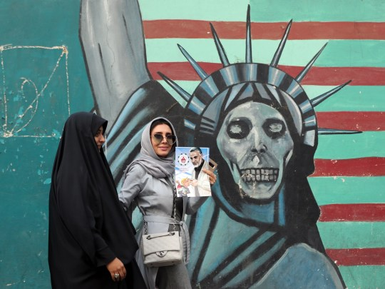 An Iranian woman holds a poster of an Iranian General of the Islamic Revolutionary Guards Corps as she walks past a mural depicting a skull-and-white Statue of Liberty near the former US Embassy in Tehran, Iran, on November 4, 2018.