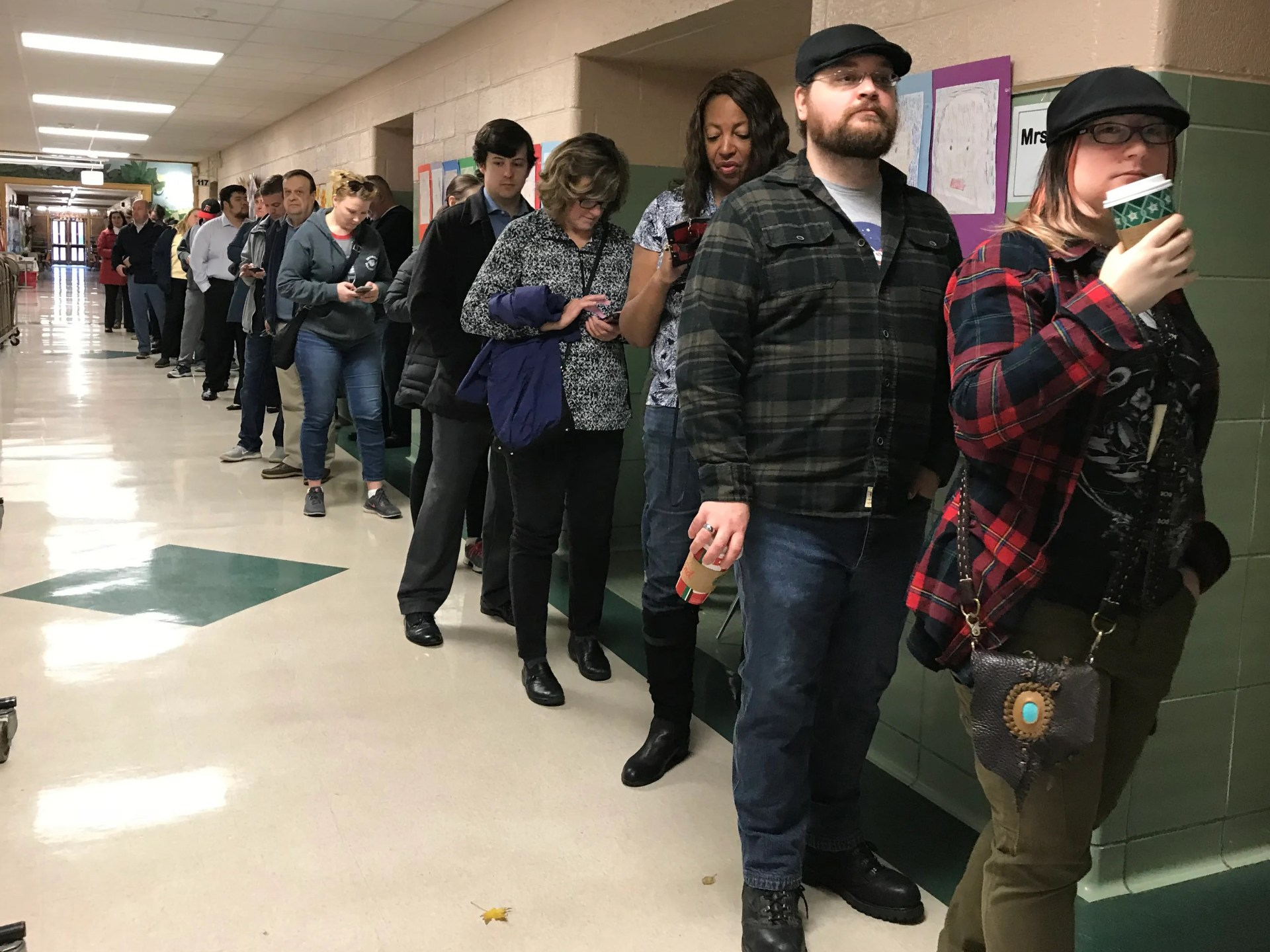 A long line of voters wait in the hallway outside the gymnasium at Monteith Elementary School to cast their ballots in the midterm election Tuesday morning in Grosse Pointe Woods, Michigan.