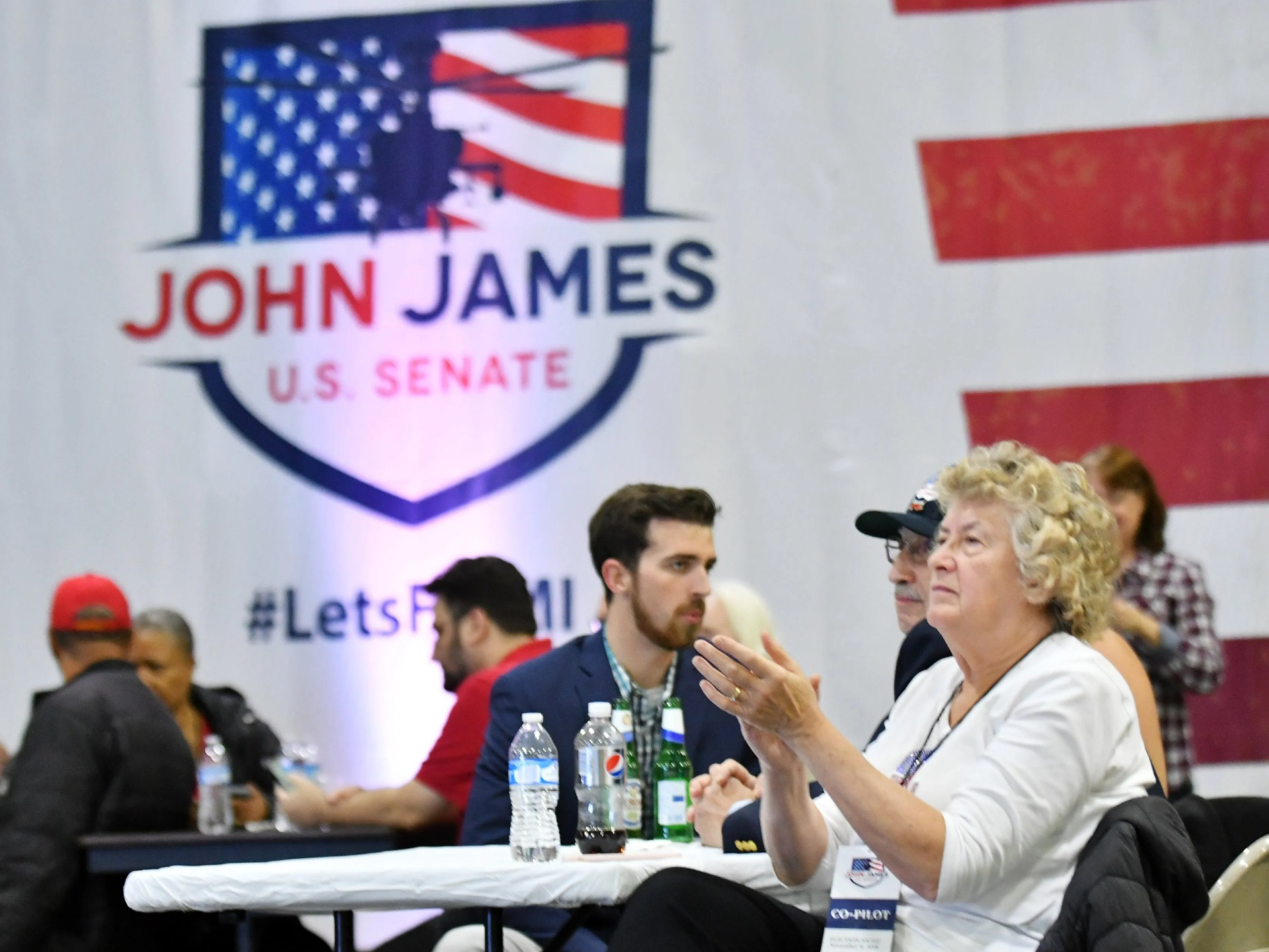 Nancy Corsett of Lexington applauds as early results are shown on television at the election night party for U.S. Senate Republican candidate John James at James Group International in Detroit Tuesday night.