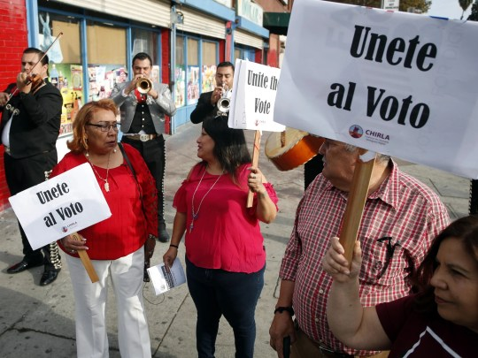 epa07145946 Latino voters Griselda Sanchez (L) and Evelyn Franco (2L) carry signs that read 'Unite the Vote' as they are serenaded by mariachis on their way to their polling station to cast their ballots in the 2018 midterm general election in Los Angeles, California, USA, 06 November 2018. Voters across the nation are selecting who will represent them on local, state and national levels.  EPA-EFE/MIKE NELSON ORG XMIT: MAN01