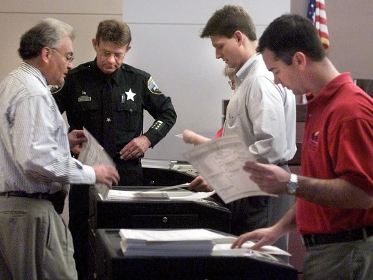 Leon County Supervisor of Elections, Ion Sancho, left, and other election officials recount general election ballots Tuesday morning at the Leon County Courthouse. The ballots were left over from the recount that was halted two weeks ago because of the Supreme Court decision.