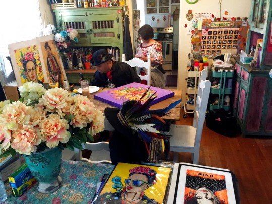 In this Thursday, April 5, 2018 photo artist Moises Salcedo, left, of Albuquerque, who goes by the name El Moises, sits amid his artwork at his home and studio.