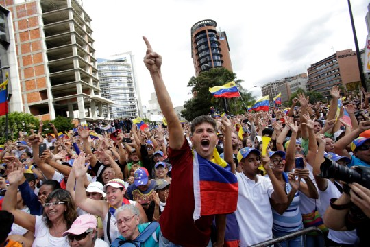 Anti-government protesters cheer after Juan Guaido, head of Venezuela's opposition-run congress, declares himself interim president of the South American country until a new election can be called, at a rally demanding the resignation of President Nicolas Maduro, in Caracas, Venezuela, Wednesday, Jan. 23, 2019.