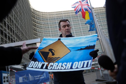 An anti-Brexit protester holds a banner as he talks to the media outside the European Commission's headquarters  in Brussels on Feb. 7, 2019.