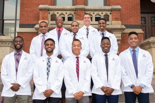 """These are the 10 black men in University of Cincinnati College of Medicine's first year class at their """"White Coat Ceremony,"""""""