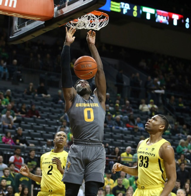 Arizona State's Luguentz Dort, center, dunks between Oregon's Louis King, left, and Francis Okoro, right, during the first half of an NCAA college basketball game Thursday, Feb. 28, 2019, in Eugene, Ore.