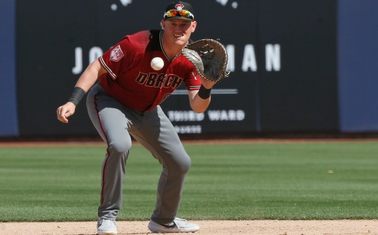 Arizona Diamondbacks first baseman Kevin Cron fields a ground ball hit by Milwaukee Brewers' Corey Ray in the seventh inning of a spring training baseball game Friday, March 8, 2019, in Phoenix.