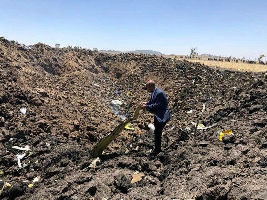 In this photo taken from the Ethiopian Airlines Facebook page, the CEO of Ethiopian Airlines, Tewolde Gebremariam, looks at the wreckage of the plane that crashed shortly after takeoff from Addis Ababa, Ethiopia, on Sunday.