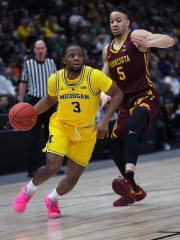 Michigan guard Zavier Simpson drives against Minnesota guard Amir Coffey during first half action of the Big Ten tournament semifinal Saturday, March 16, 2019 at the United Center in Chicago.