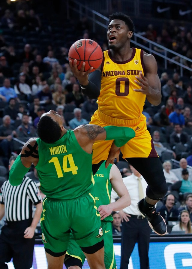 Arizona State's Luguentz Dort (0) fouls Oregon's Kenny Wooten during the first half of an NCAA college basketball game in the semifinals of the Pac-12 men's tournament Friday, March 15, 2019, in Las Vegas. (AP Photo/John Locher)