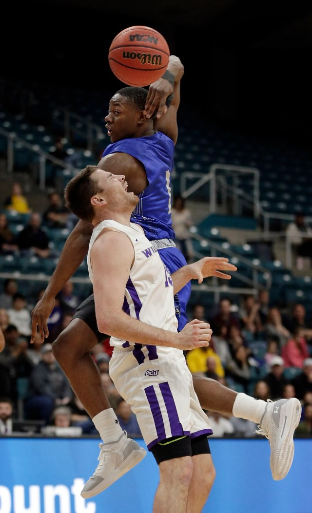 New Orleans guard Damion Rosser (1) passes the ball over Abilene Christian forward Hayden Farquhar, front, during the first half of an NCAA college basketball game for the Southland Conference men's tournament title Saturday, March 16, 2019, in Katy, Texas.