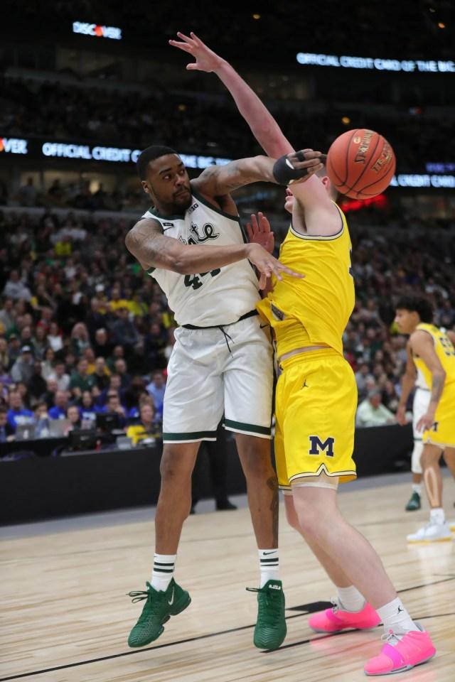 Michigan State's Nick Ward passes around Michigan's Jon Teske during Big Ten tournament championship Sunday, March 17, 2019 in Chicago.