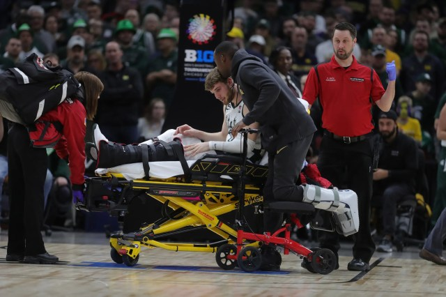 Michigan State's Joshua Langford kisses teammate Kyle Ahrens as he is taken off the court with a foot injury against Michigan in the Big Ten tournament championship Sunday, March 17, 2019 in Chicago.