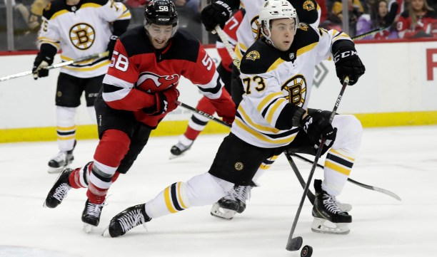 Boston Bruins defenseman Charlie McAvoy (73) stops a shot as New Jersey Devils center Kevin Rooney (58) watches during the second period of an NHL hockey game Thursday, March 21, 2019, in Newark, N.J.