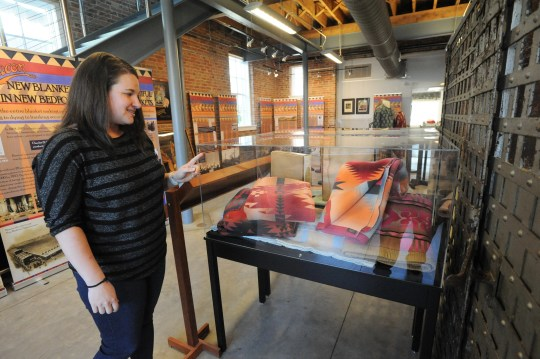 Swannanoa Valley Museum and History Center director Anne Chesky Smith talks about a display featuring blankets from Beacon Manufacturing, which is the focus of the museum's major exhibit this season. SVM will open its doors for the 30th year on April 13.