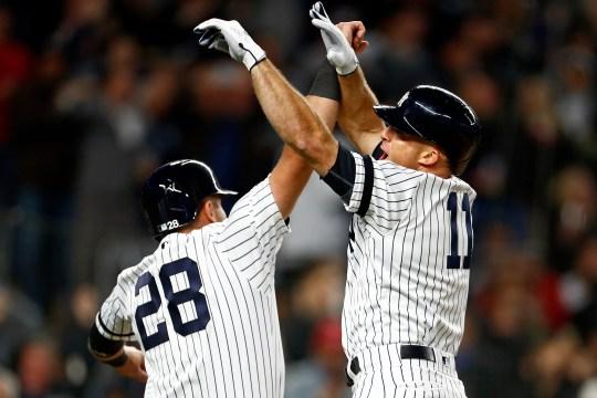 New York Yankees left fielder Brett Gardner (11) celebrates his grand slam with catcher Austin Romine.