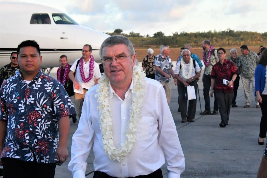 Wearing a fresh lei draped upon him moments before, International Olympic Committee president Thomas Bach heads to his motorcade after his arrival on the tarmac of the A.B. Won Pat Guam International Airport on May 10, 2019.