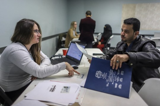 Volunteer attorney Tania Morris Diaz, of Michigan Immigration Rights Center, works with Hameed Alsobhi, 33, of Hamtramck, on his citizenship application, during the Detroit New Americans campaign's citizenship workshop at the Yemeni American Leadership Association in Hamtramck on April 26.