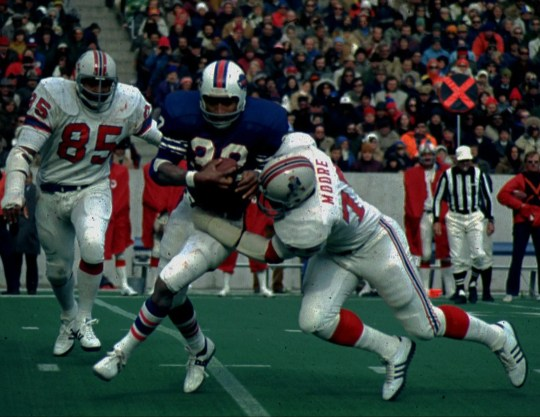 Former Buffalo Bills running back O.J. Simpson (32) attempts to break a tackle by New England Patriots Arthur Moore, as Patriots Julius Adams (85) moves in, in this 1974 file photo.