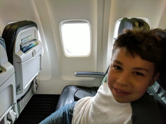 Iden Elliott stakes out his seat on a flight from Seattle to Anchorage in 2017.