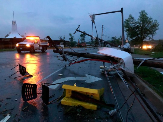Plastic chairs lie in the road and metal from a damaged gas station roof is twisted around a downed power line in Jefferson City Missouri Thursday, May 23, 2019. The National Weather Service has confirmed a large and destructive tornado has touched down in Missouri's state capital, causing heavy damage and trapping multiple people in the wreckage of their homes. (AP Photo/David A. Lieb) ORG XMIT: TKSK115