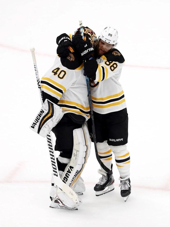 Tuukka Rask (40) and David Pastrnak (88) celebrate the Bruins' win over the Blues.