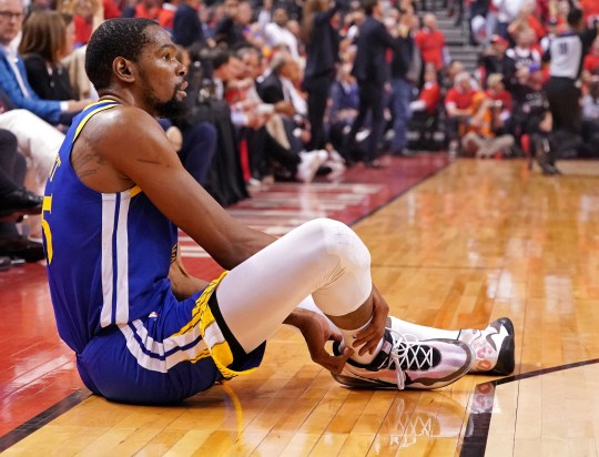Kevin Durant sits on the court after suffering an Achilles injury.