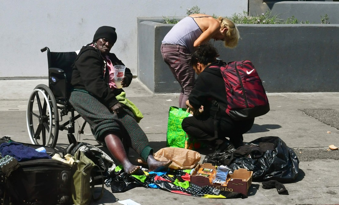 A homeless woman looks on from her wheelchair as others rummage through their belongings in Los Angeles. The city of Los Angeles on May 29 agreed to allow homeless people on Skid Row to keep their property and not have it seized.