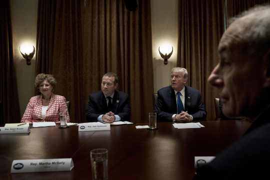 Rep. Susan Brooks (Republican from Indiana), Rep. Josh Gottheimer (Democrat from New Jersey -L), US President Donald Trump and White House Chief of Staff John Kelly wait for a meeting with lawmakers in the Cabinet Room of the White House on September 13, 2017 in Washington, DC.