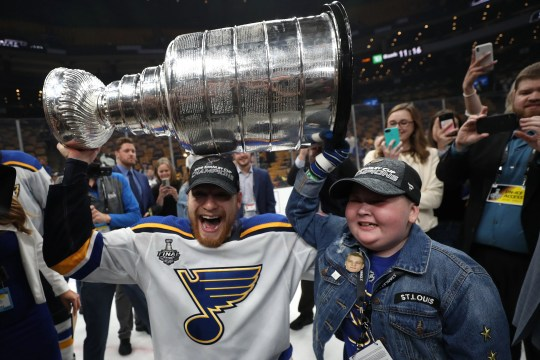 Colton Parayko lifts the Cup with Laila Anderson, who's battling a rare disease and has helped inspired the team.