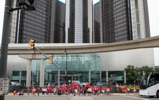 Группа протестующих против UAW машет рукой проезжающим машинам, когда General Motors и UAW открывают переговоры по контракту 2019 года о новом национальном соглашении во вторник, 16 июля, в Ренессанс-центре Детройта Marriott 2019.