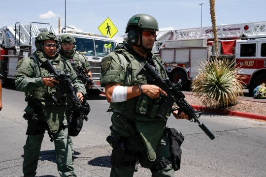 Heavily armed SWAT and El Paso County Sheriff's Office officers head toward an East El Paso Walmart where a gunman attacked Saturday, Aug. 3, 2019.