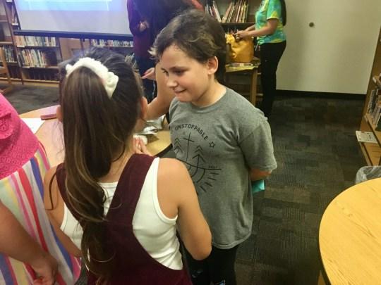 Isabella McCune habla con sus compañeros de clase después de una presentación del personal en el Centro de quemaduras de Arizona para explicar sus heridas.
