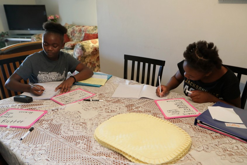 "Sisters Nseya ""Ruthie"" Ntambwe, 16, left, and Nsamba ""Joyce"" Kaikamba, 14, both Congolese refugees, write cooking-related vocabulary terms in their notebooks after learning them from Yennifer Castillo, a Florida A&M student and International Rescue Committee (IRC) volunteer, teaches language and culture the sisters at their home Friday, August 16, 2019."